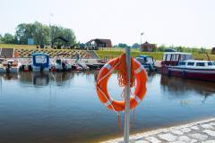 na pierwszym planie koło ratunkowe na drugim jezioro z zabudoaniami przystani i łódka
