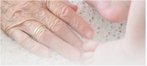 Na białej tkaninie ręka starszego człowieka i stopy maluszka