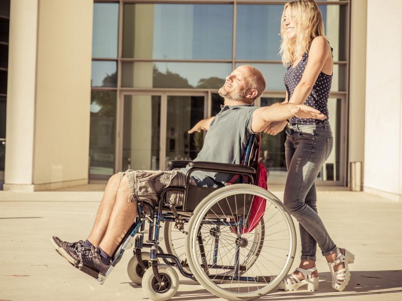 Zdjęcie - uśmiechnięta kobieta pcha mężczyznę siedzącego na wózku inwalidzkim