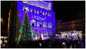 Zdjęcie przedstawia tłum ludzi zgromadzonych przed poznańskim Ratuszem. Budynek jest podświetlony na niebiesko