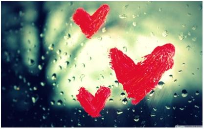 Na zdjęciu trzy serca namalowane szminką na szybie, po której spływają krople deszczu