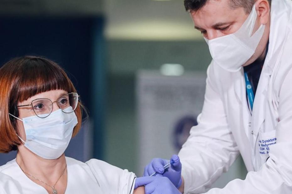 Zdjęcie, lekarz szczepi kobietę, która podniosła rękę z uniesionym do góry kciukiem