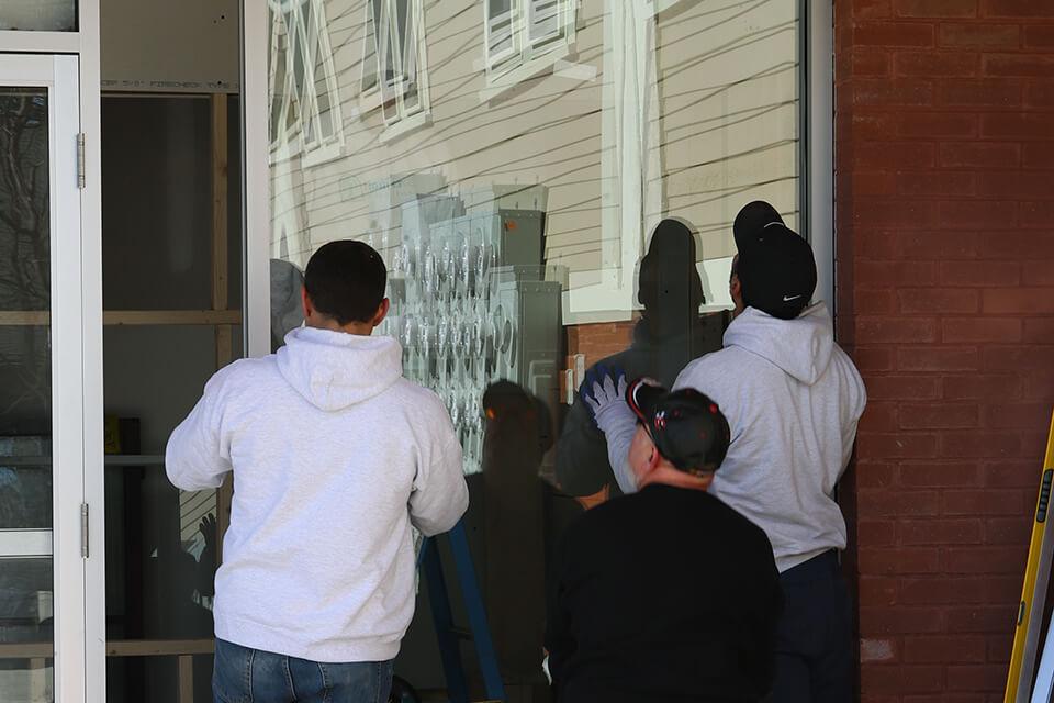 Pioneer Employees Looking at Installed Door Glass