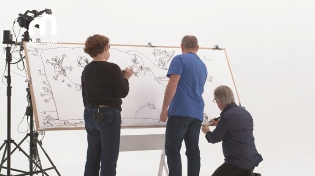 The artists draw on the big board together