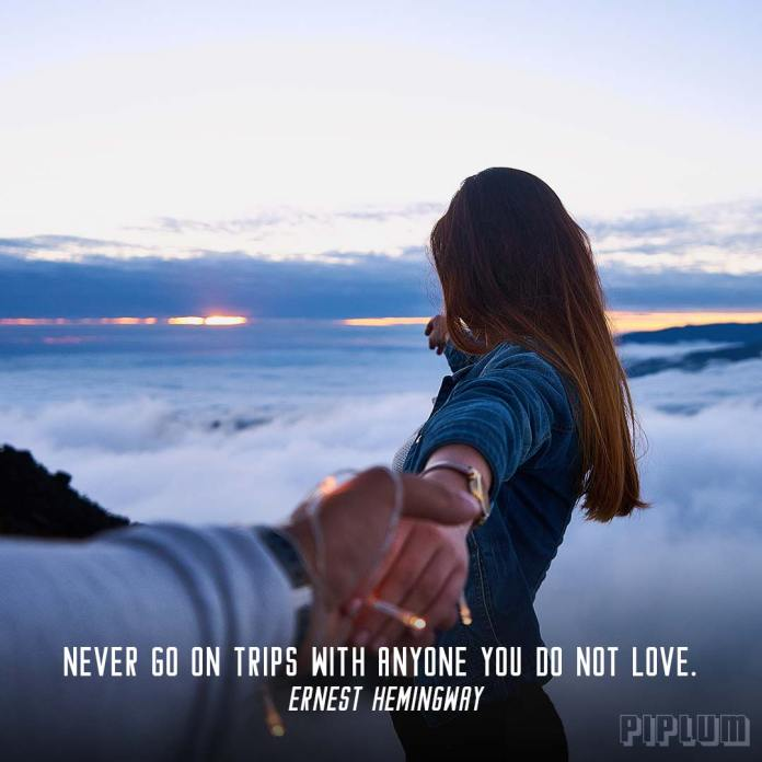 Love quote. Man holding his girlfriend hand on the top of the mountain.