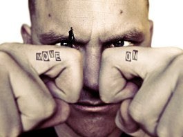 Man face with bended fingers in front. Text tatoos on each