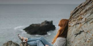 Inspirational Quote. Redhead women sitting on the rocks and looking towards ocean.