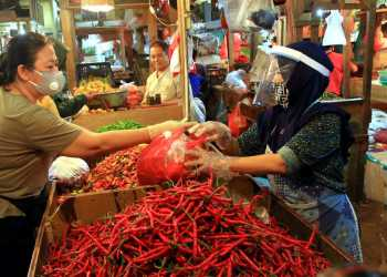 Pedagang menggunakan penutup muka melayani pembeli di Pasar Senen,  Jakarta Pusat,  Selasa (1/5/2002). Kemendag menyiapkan pedoman bagi penyelenggara kegiatan perdagangan untuk diterapkan saat berlangsungnya new normal, para pedagang di pasar rakyat diwajibkan nenggunakan masker, face shield, dan sarung tangan selama beraktivitas. SP/Joanito De Saojoao.