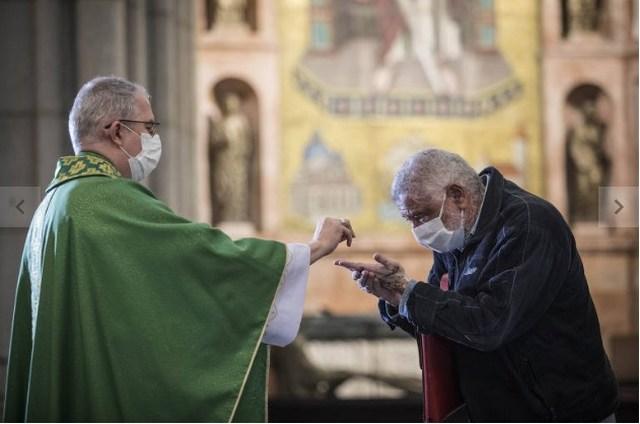 Fiel precisa higienizar mãos para comungar na volta das missas em SP