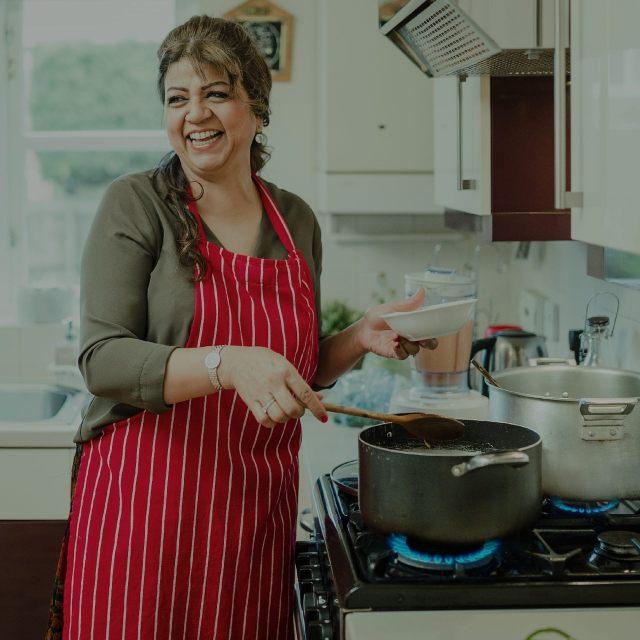Uma foto de uma mulher cozinhando com o gás natural encanado da Comgás