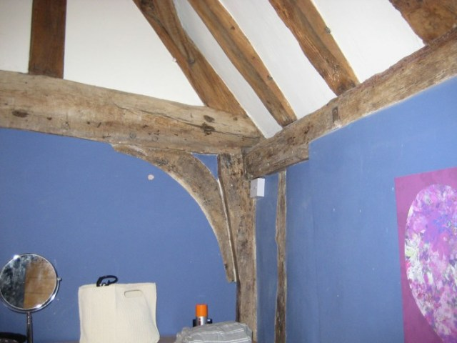 The cross wing central tie beam at first floor level showing the lack of studs and decorative curved braces indicating that this room was open as a single room with central exposed truss. The side wall contains the chimney breast which was inserted later.