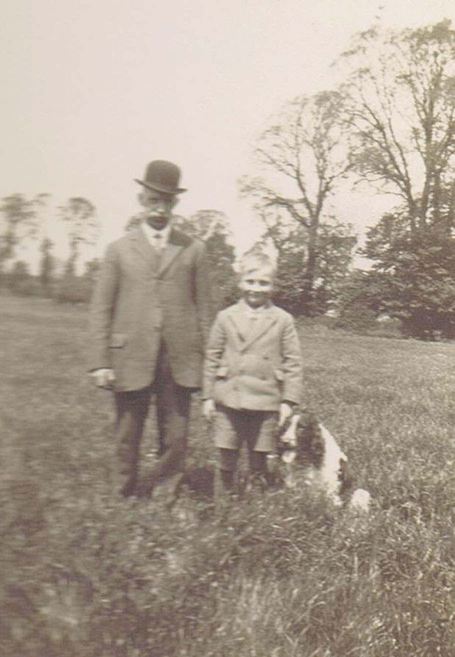 George Weedon and his grandson Bernard Lake.The picture is taken in the middle of the meadow behind 28 and 30 Shillington Road. The tall foreground trees on the right are elms, which died from Dutch Elm Disease in the 1970s. The moderately tall trees beyond them are pear trees in the old Wright's Farm orchard. The bushes just to the left of George's right elbow are brambles on the corner of the orchard, where the meadow boundary makes a dog-leg and the culvert under the meadow comes out, wrongly marked as a spring on the Ordnance maps.