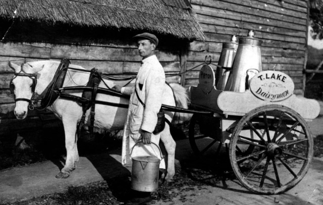 "1926 Tom Lake, Pirton's first milkman, with his churns, pails and measuring jugs. He delivered milk twice a day as there were no fridges to keep milk cool. Milk was ""straight from the cow"" and was not pasteurised as is now required by health legislation"