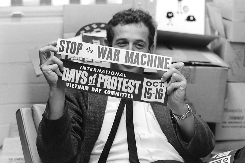 "Edward Sampson, Associate Professor of Social Psychology, holds two bumper stickers: ""International Days of Protest Vietnam Day Committee, Oct. 15–16"" and ""Stop the War Machine."" Taken September 16, 1965 in his office."
