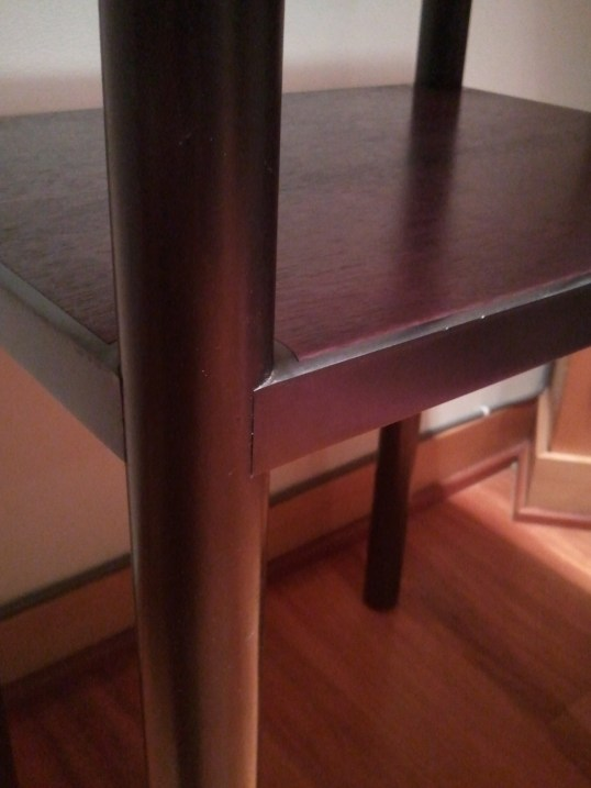 Shelf frame hugs table leg