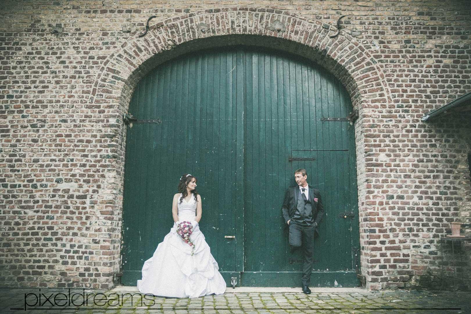 Ein tolles Hochzeitsfoto im Vintage Look. Brautpaar steht vor einem Tor und schaut sich an.