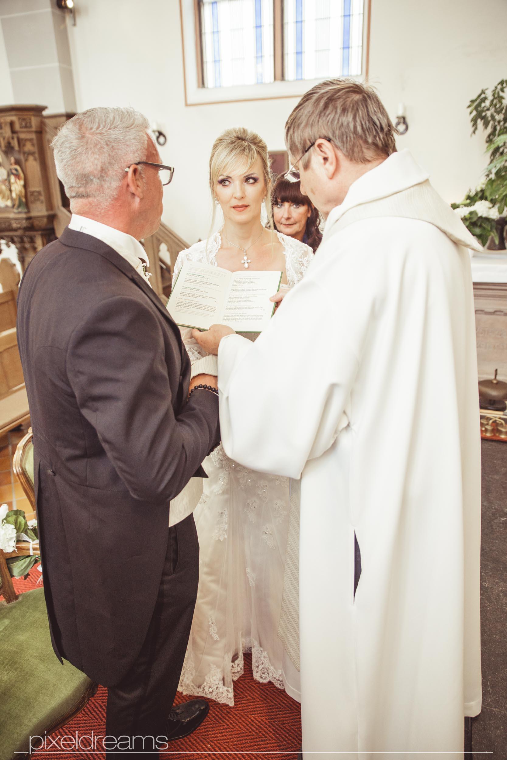 Kirchliche Trauung in der St. Antonius Kirche Swisttal. Hochzeitsfotograf hält den Moment des Gelübtes fest.