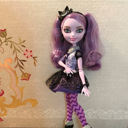 Kitty Cheshire Doll Posing With Grey Background