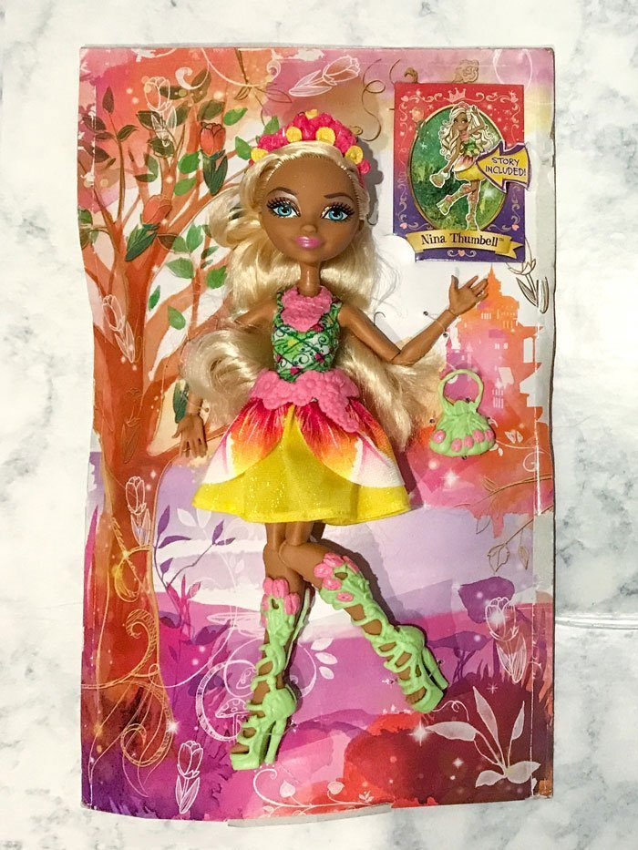 Nina Thmbell doll attached to packaging.
