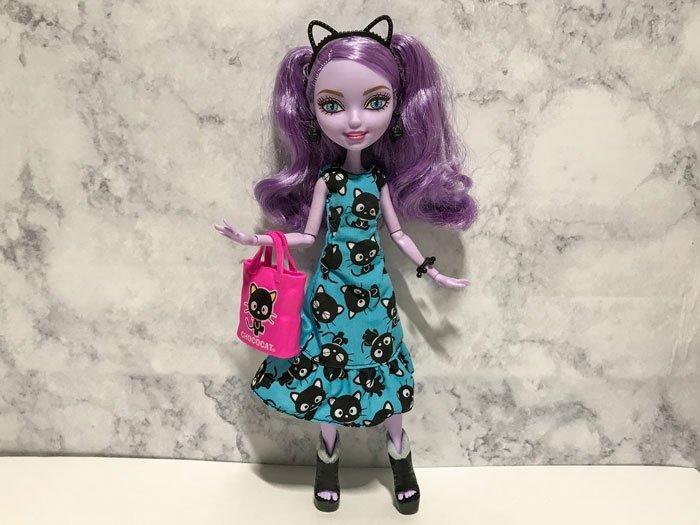 Kitty Cheshire wearing Hello Kitty dress, headband, and tote.