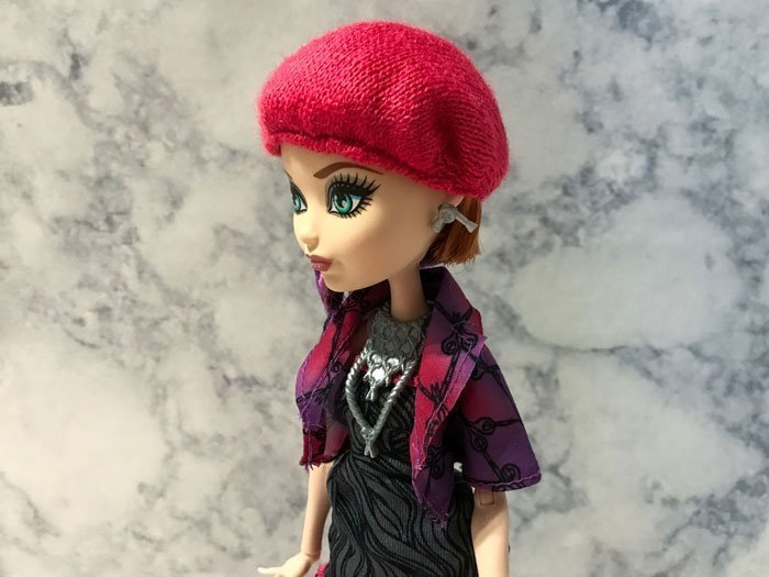 Poppy's pink beret is elasticized and fits snugly around her head.