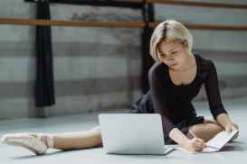 busy ethnic woman using laptop in dance hall