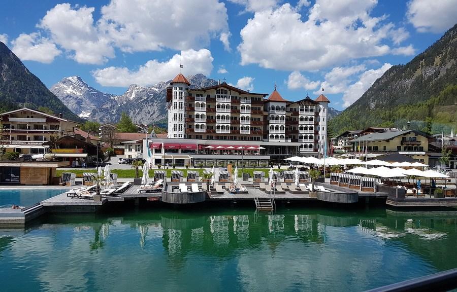 Blick auf Hotel Entner's am See mit Pool und weiter hinten die mächtigen Gipfel des Karwendel