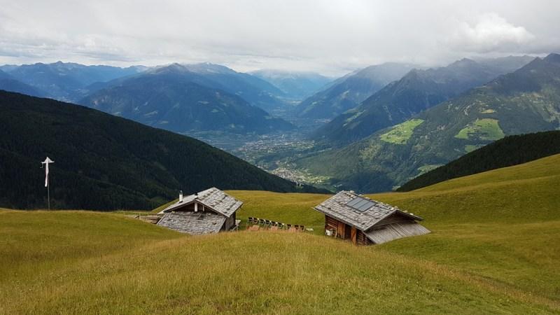 Ausblick auf die beiden Gebäude der Assenhütte und das herrliche Panorama mit Meran, Texel- und Ortlergruppe sowie dem Vinschgau