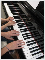 Hands playing piano. For whom are we singing