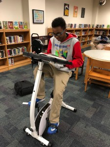 Photo of a student reading and riding a stationery bike