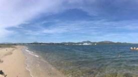 Pláž nedaleko letiště Olbia s výhledem na trajekty