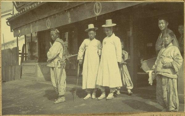 Une photo de deux hommes jungin (au milieu) en tenue blanche, les années 1900