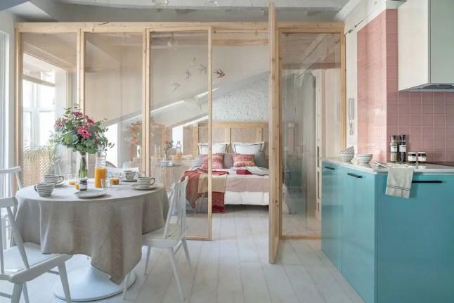 Une cuisine couleur pastel et une verrière en bois dans un petit appartement sous les toits
