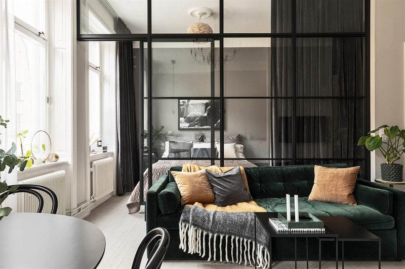 Verrière, canapé en velours et décoration actuelle dans un deux-pièces de 42m2