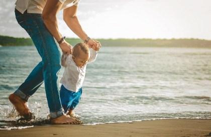 un papa et son enfant à la plage