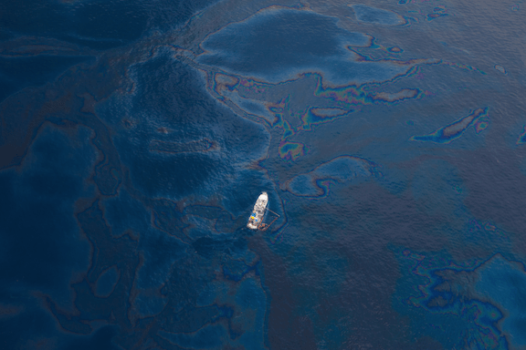 A ship floats amongst a sea of spilled oil in the Gulf of Mexico after the BP Deepwater Horizon oilspill disaster. Date: June 16, 2010. (Image Credit: Kris Krüg)