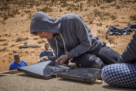 Alex installing solar panels on the roof of a Navajo house (Source: the Honnold Foundation)