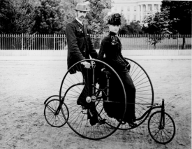 A couple seated on an 1886 Coventry Rotary Quadracycle for two. (Image: Public Domain)