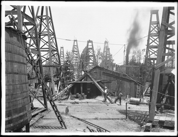 Two men standing near a wooden shed in the midst of dozens of oil derricks in a Los Angeles oil field. (Image Credit: WikiMedia Commons)