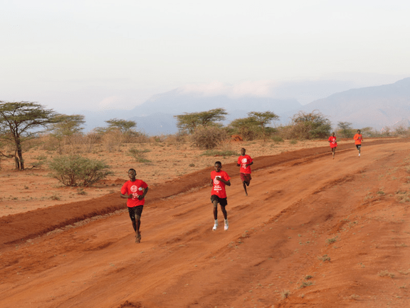 Runners pass Checkpoint 2 in the Running For Lions half marathon in northern Kenya. (Image Credit: Ewaso Lions)
