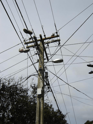Utility pole supporting wires for electrical power distribution, coaxial cable for Cable TV and telephone cable. (Photo: WikiMedia Commons)