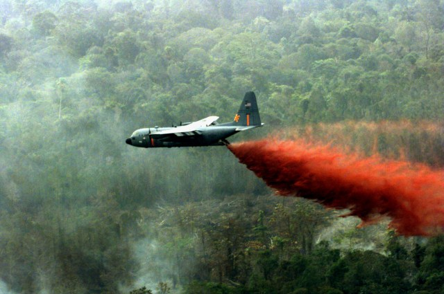 A Wyoming Air National Guard C-130 Hercules drops a water and fire retardant slurry on a fire on the Indonesian island of Sumatra on Nov. 17, 1997. Three C-130s and a total of 96 service members were sent to Indonesia for humanitarian support in fighting the jungle fires that year. (Photo Credit: Staff Sgt. Daryl McKamey, Air National Guard)