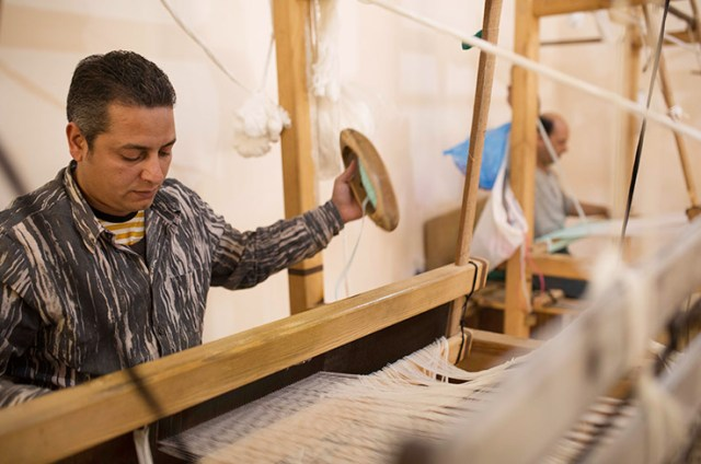 One of Reform Studio's employees uses the handloom to weave plastic bags into upholstery for designer furniture. (Photo Credit: Sabry Khaled / CC BY-NC-ND)