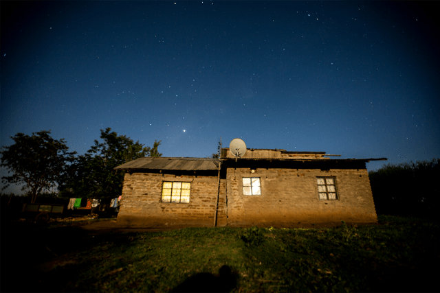 Rural house with Azuri TV at night. (Photo courtesy of Azuri)