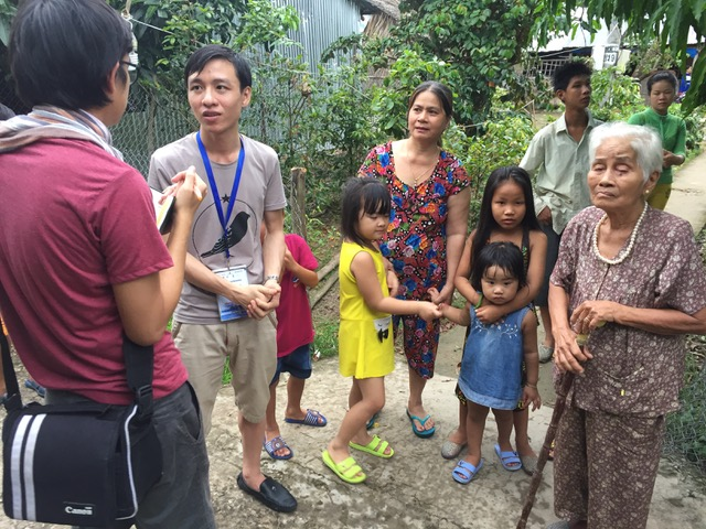 A journalist interviews Mekong residents struggling with erosion and water levels. (Photo: Adam Hunt / The Mekong Eye)