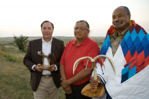 Standing Rock Sioux Tribe Council Representative, Jesse Taken Alive (center), honors FEMA Region VIII Regional Administrator, Robert Flowers (left) and FEMA Tribal Region VIII Tribal Liaison Officer, Scott Logan (right), during the ten year commemoration of the FEMA Tribal Relations policy. (Photo Credit: Andrea Booher / FEMA Photo Library)