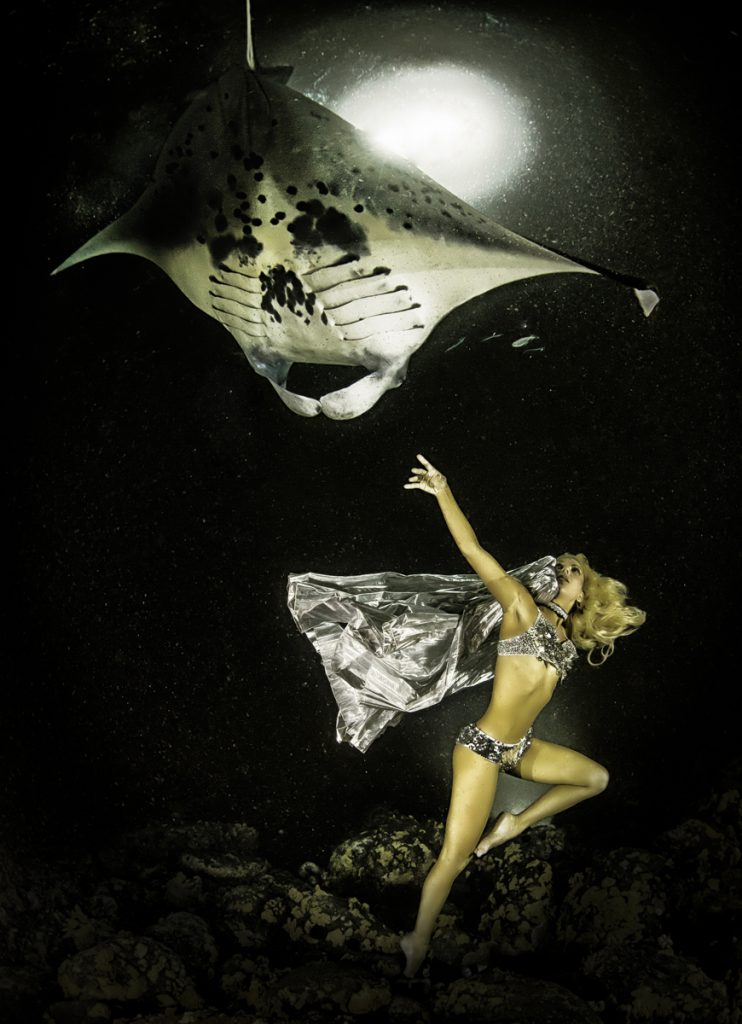 A ray of hope for mantas is CITES. Here, Hannah Mermaid dances with a manta on a full-moon night. Photo by Shawn Heinrichs.