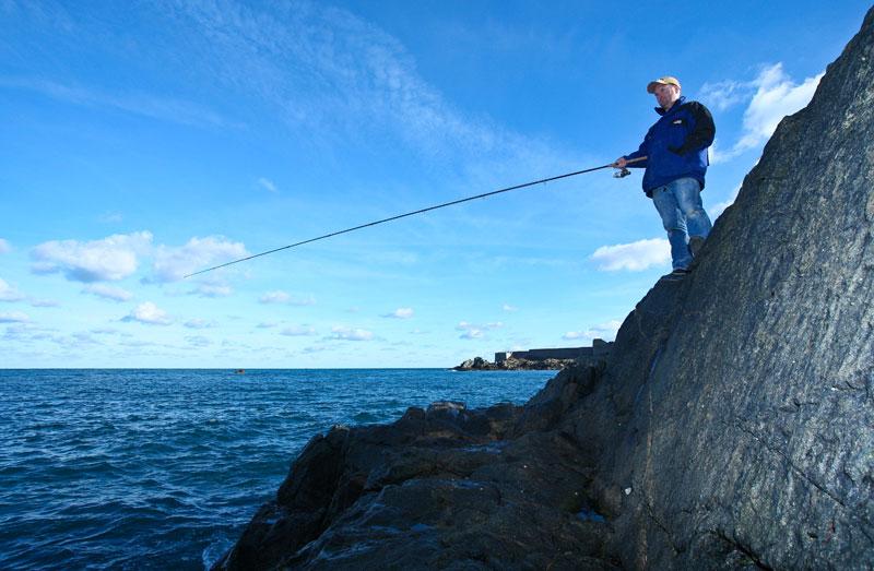 an angler with a float rod for Alderney mullet