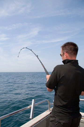 an angler in black fights a fish with rod bent