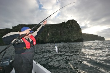 an angler fishes from a small boat under cliffs